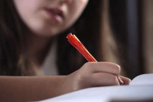 Young girl writing whilst studying or doing homework